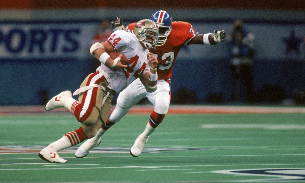 . Full back Tom Rathman #44 of the San Francisco 49ers looks for room to run against the Denver Broncos defense in Super Bowl XXIV at Louisiana Superdome on January 28, 1990 in New Orleans, Louisiana.  The 49ers won 55-10.  (Photo by George Rose/Getty Images)