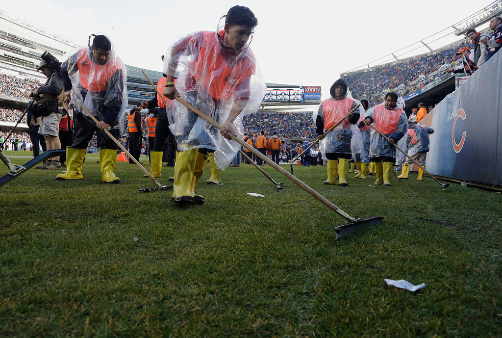. Soldier Field\'s ground crew prepares the field to resume play after a severe storm blew through the area and suspended play during the first half of an NFL football game between the Chicago Bears and Baltimore Ravens, Sunday, Nov. 17, 2013, in Chicago. (AP Photo/Nam Y. Huh)