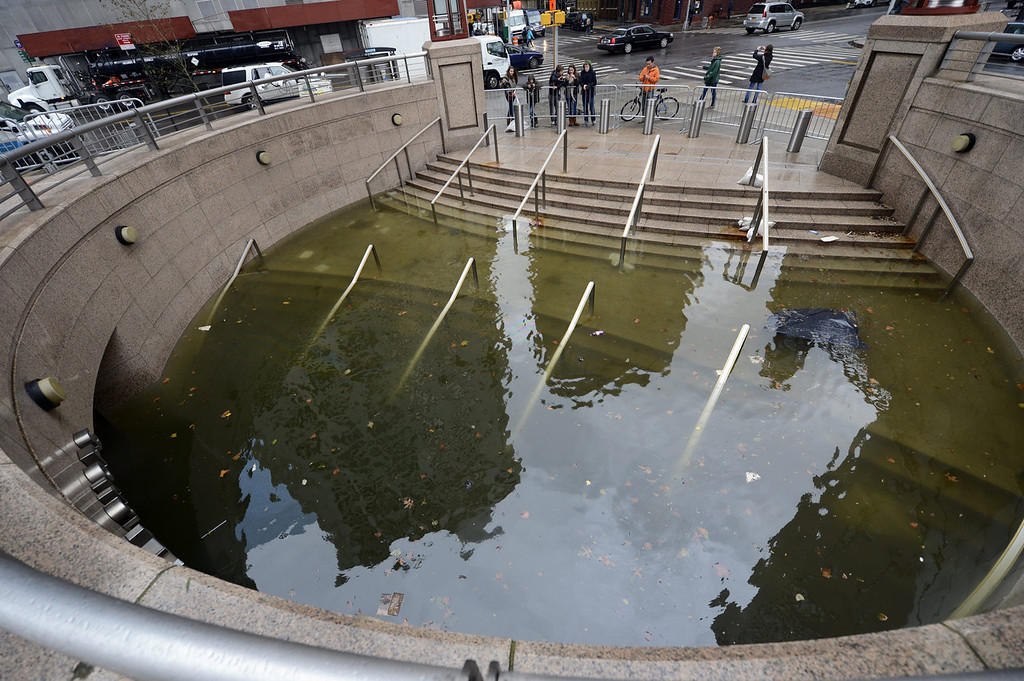 . People take photos of water filling the entrance of The Plaza Shops in Battery Park in New York on October 30, 2012 as New Yorkers cope with the aftermath of Hurricane Sandy. The storm left large parts of New York City without power and transportation.     AFP PHOTO / TIMOTHY A. CLARY