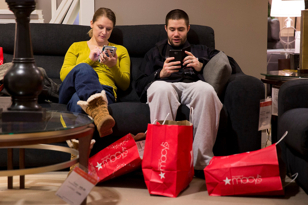 . Andrea and Karl Galvez of Chicago take a break from shopping during Black Friday shopping at Macy\'s on Friday, Nov. 29, 2013, in Chicago.Black Friday, the day after Thanksgiving, is typically the nation\'s biggest shopping day of the year. (AP Photo/Andrew A. Nelles)