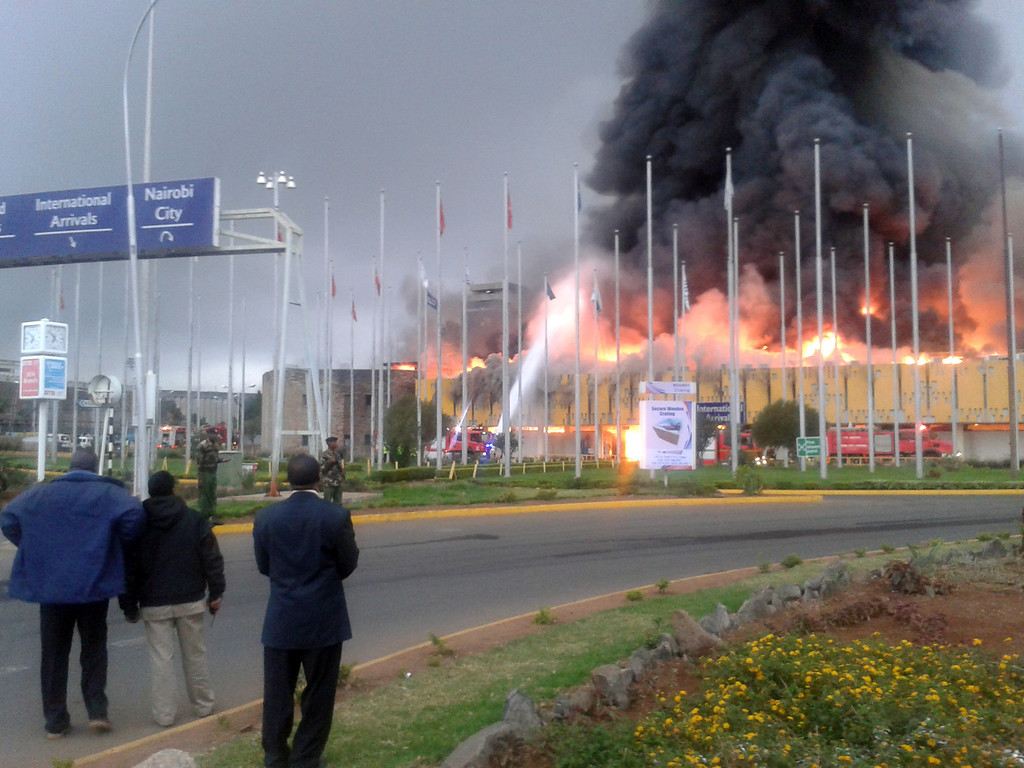 . Onlookers watch as black smoke billows from the international arrival unit  of Jomo Kenyatta International Airport in Nairobi, Kenya, Wednesday, Aug. 7, 2013. A massive fire engulfed the arrivals hall at Kenya\'s main international airport early Wednesday, forcing East Africa\'s largest airport to close and the rerouting of all inbound flights. (AP Photo/Segeni Ngethe)