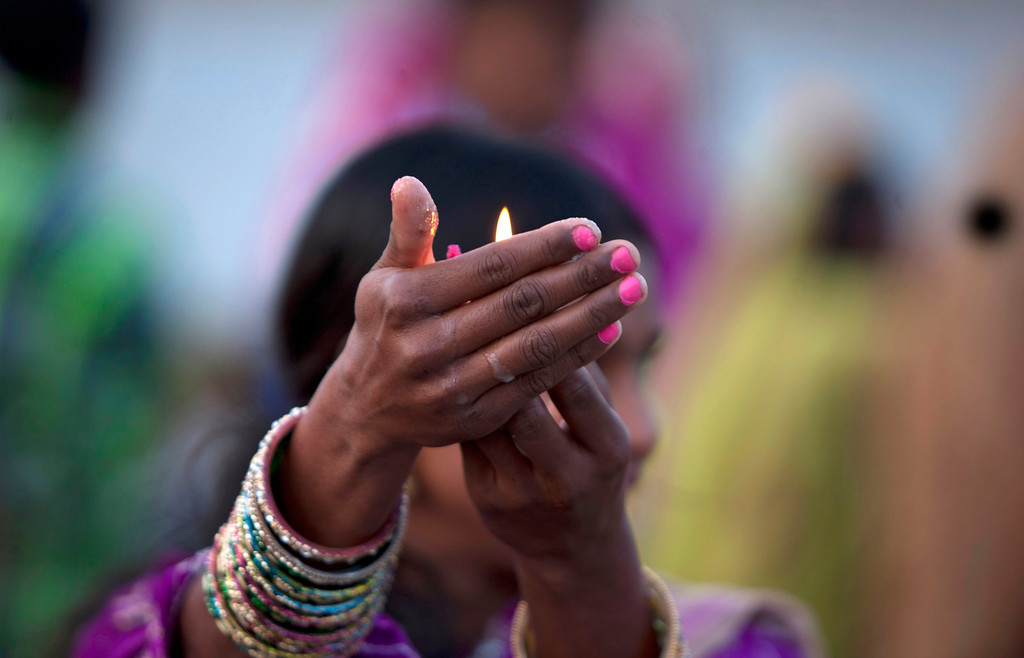 . A Hindu devotee performs rituals at sunset in the Tawi River during Chhath Puja festival in Jammu, India, Friday, Nov. 8, 2013. (AP Photo/Channi Anand)