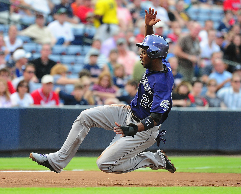 . Dexter Fowler #24 of the Colorado Rockies slides safely in to third base against the Atlanta Braves at Turner Field on July 30, 2013 in Atlanta, Georgia. (Photo by Scott Cunningham/Getty Images)