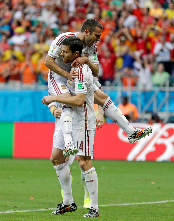 . Spain\'s Xabi Alonso is congratulated by his teammate Jordi Alba  after scoring on a penalty kick during the  first half of group B World Cup soccer match between Spain and the Netherlands at the Arena Ponte Nova in Salvador, Brazil, Friday, June 13, 2014.  (AP Photo/Natacha Pisarenko)
