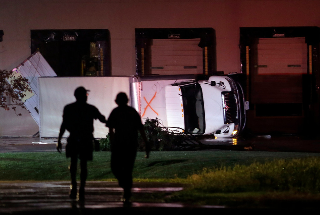. People walk near an overturned truck in an industrial park after strong storms moved through the area Friday, May 31, 2013, in St. Louis. (AP Photo/Jeff Roberson)