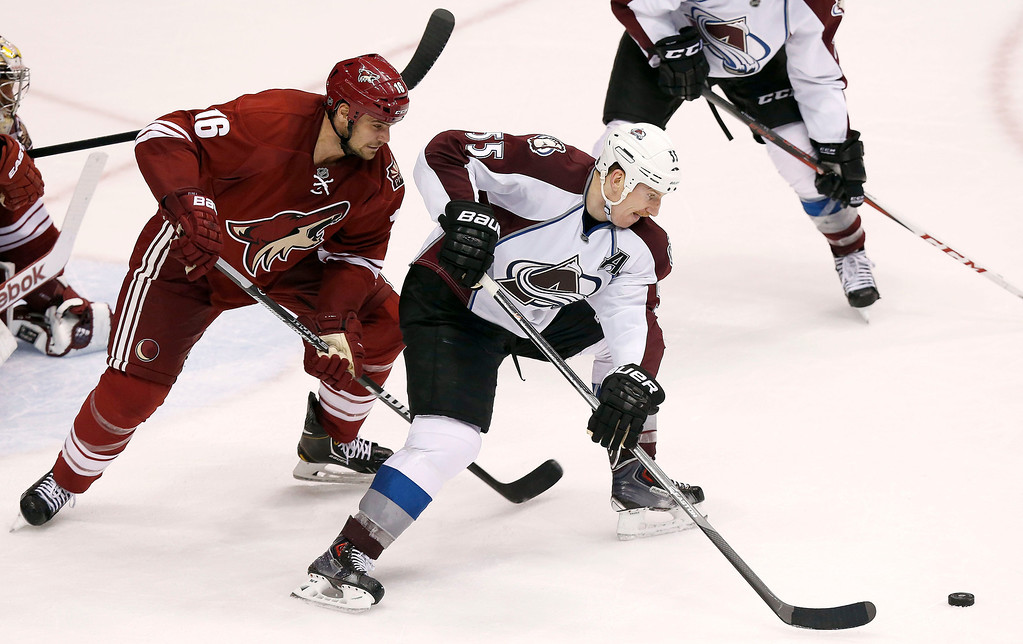 . Colorado Avalanche\'s Cody McLeod (55) gathers the puck before a backhand shot for a goal in front of Phoenix Coyotes\' Rostislav Klesla (16), of the Czech Republic, during the third period of an NHL hockey game Thursday, Nov. 21, 2013, in Glendale, Ariz.  The Avalanche defeated the Coyotes 4-3. (AP Photo/Ross D. Franklin)