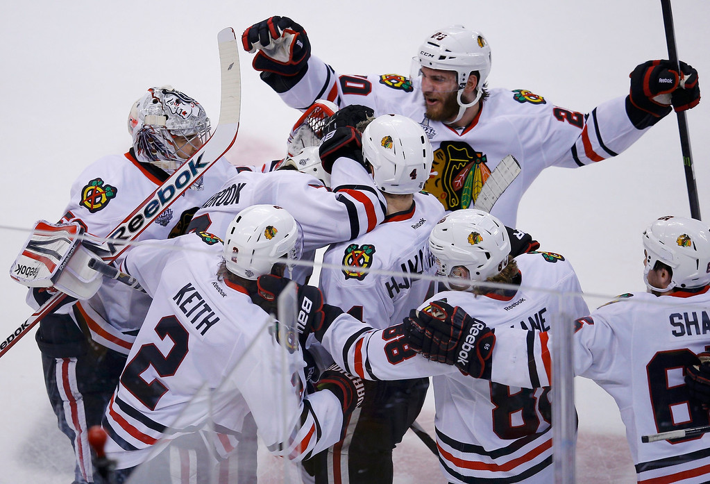 . The Chicago Blackhawks celebrate after Brent Seabrook (7) scored in overtime on the Boston Bruins to win Game 4 of their NHL Stanley Cup Finals hockey series in Boston, Massachusetts, June 19, 2013. REUTERS/Brian Snyder