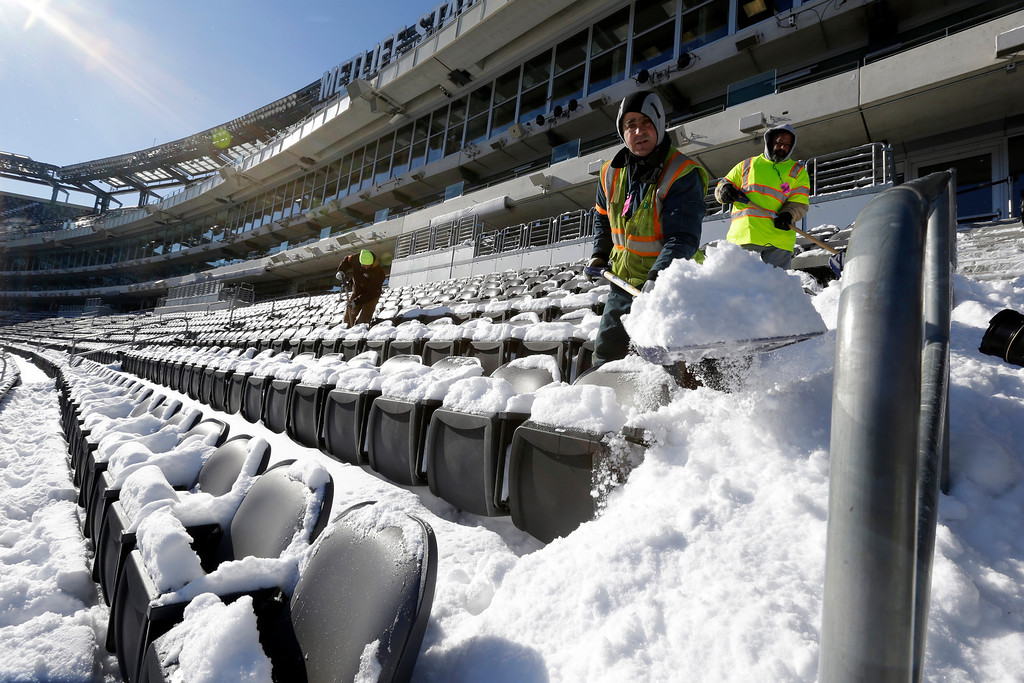 . Workers shovel snow off the seating area at MetLife Stadium as crews removed snow ahead of Super Bowl XLVIII following a snow storm, Wednesday, Jan. 22, 2014, in East Rutherford, N.J. Super Bowl XLVIII, which will be played between the Denver Broncos and the Seattle Seahawks on Feb. 2, will be the first NFL title game held outdoors in a city where it snows. (AP Photo/Julio Cortez)