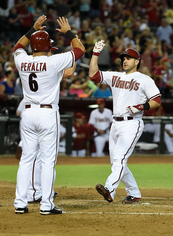 . Miguel Montero #26 of the Arizona Diamondbacks and teammate David Peralta #6 celebrate a first inning home run against the Colorado Rockies at Chase Field on August 8, 2014 in Phoenix, Arizona.  (Photo by Norm Hall/Getty Images)