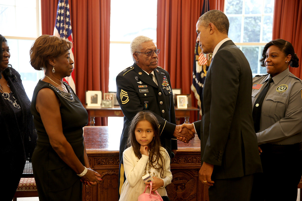 . President Barack Obama shakes hands with U.S. Army Staff Sgt. (Ret.) Melvin Morris, a Vietnam War veteran, in the Oval office as his family looks on before presenting him with the Medal of Honor at a ceremony in the White House on March 18, 2014 in Washington, DC.  Melvin Morris,  U.S. Army Sgt. First Class (Ret.) Jose Rodela and U.S. Army Specialist Four (Ret.) Santiago J. Erevia were joined by families of 21 others who were presented posthumously with the Medal of Honor for conspicuous gallantry.   (Photo by Joe Raedle/Getty Images)