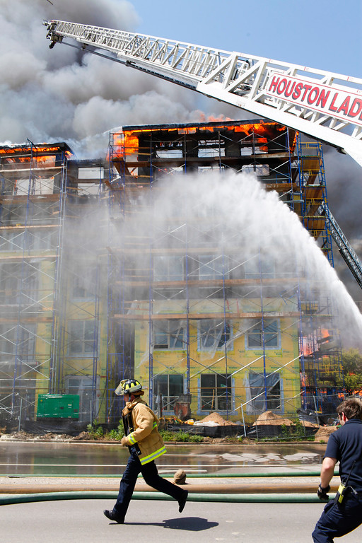 . Houston firefighters work to extinguish a five-alarm fire at a construction site Tuesday, March 25, 2014, in Houston. (AP Photo/Houston Chronicle, Eric Kayne)