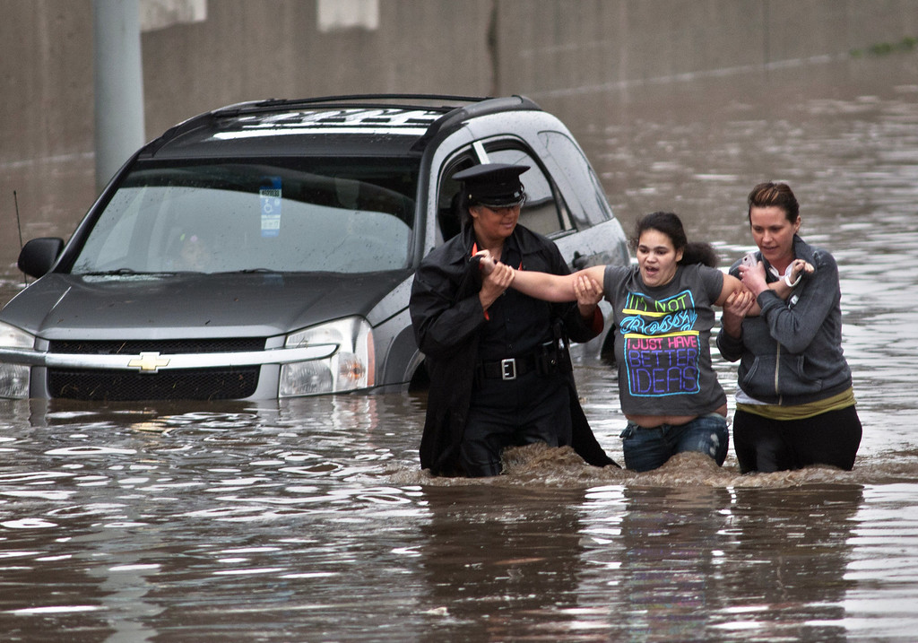 . Police officer Shannon Vandenheuvel, left, and Melissa Kolenda, right, help Barbara Jones from her partially submerged car in Grand Rapids, Mich. Thursday, April 18, 2013. Middle America was getting everything nature has to throw at it on Thursday, from snow in the north to tornadoes in the Plains, and with torrential rains causing floods and transportation chaos in several states. (AP Photo/Grand Rapids Press, Chris Clark)
