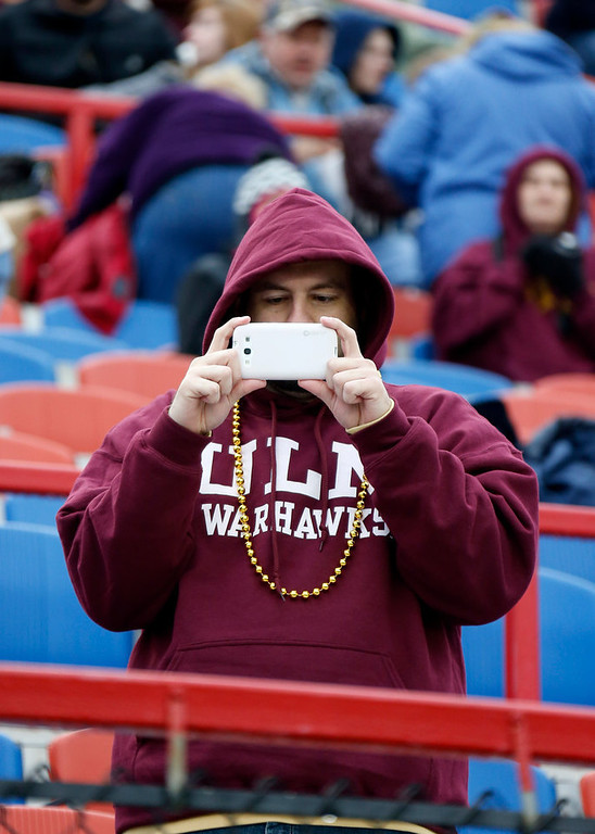 . A Louisiana-Monroe fan uses his smartphone to take a photograph of their band marching during the pregame show at the  Independence Bowl NCAA college football game featuring Ohio and Louisiana-Monroe in Shreveport, La., Friday, Dec. 28, 2012. (AP Photo/Rogelio V. Solis)
