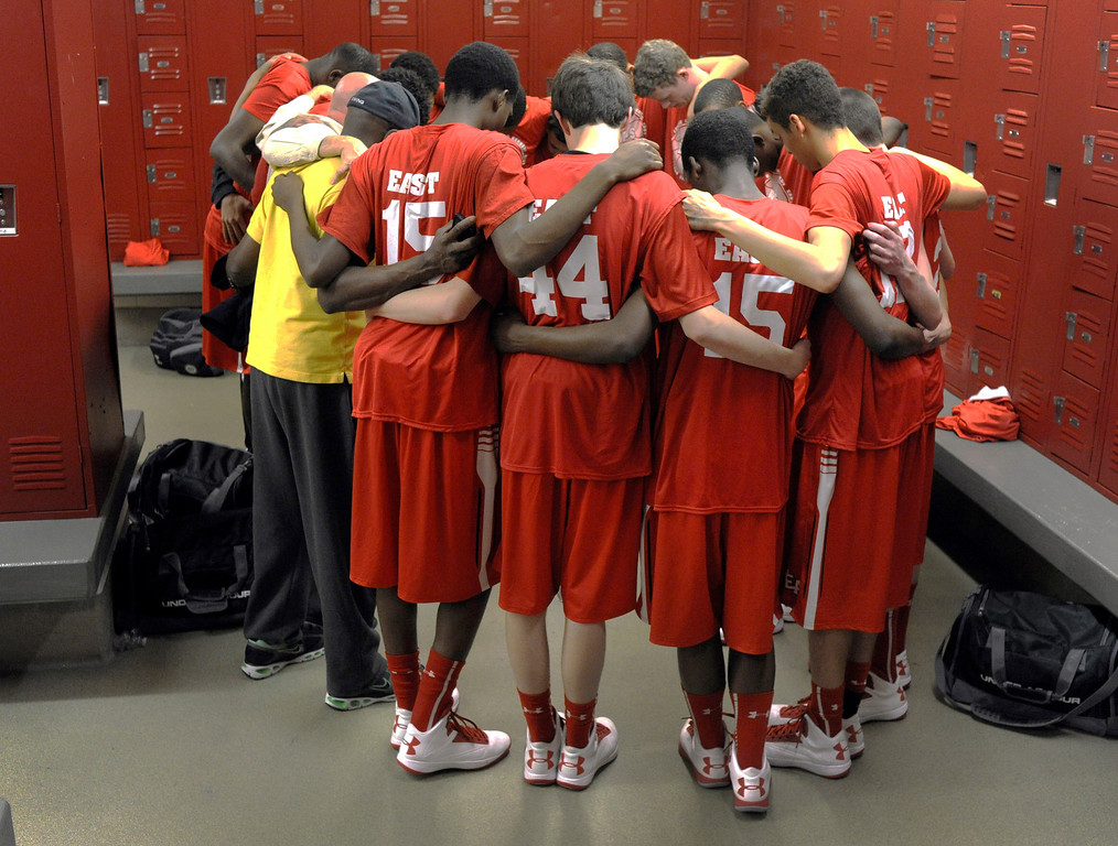 . DENVER, CO. - FEBRUARY 16: Denver East players gathered in prayer before the game. The Denver East High School boy\'s basketball team defeated George Washington 82-20 Saturday afternoon, February 16, 2013.  (Photo By Karl Gehring/The Denver Post)