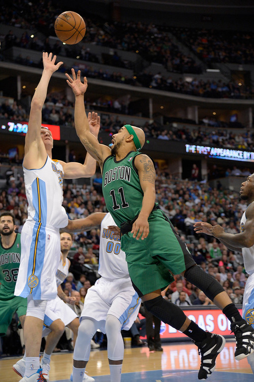 . Boston Celtics point guard Jerryd Bayless (11) takes a shot over Denver Nuggets center Timofey Mozgov (25) during the third quarter January 7, 2014 at Pepsi Center. (Photo by John Leyba/The Denver Post)