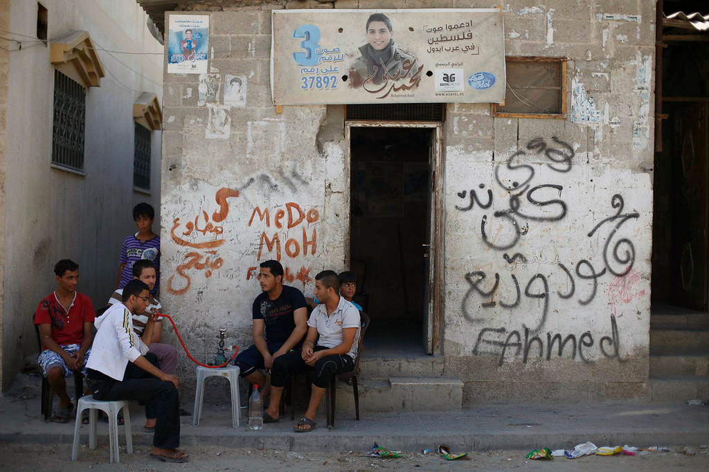 ". Palestinians smoke nargila as a poster depicting singer Mohammed Assaf is pictured on a wall of a house in Khan Younis in the southern Gaza Strip on June 20, 2013. Palestinian fans and big business are rallying behind Assaf, a 23-year-old singer from the Gaza Strip, in a final push to vote him the next ""Arab Idol\"" in a TV talent contest choosing a winner in Beirut on Saturday. The Arabic words on the right side of the poster read: \""Support the voice of Palestine in Arab Idol.\"" REUTERS/Ibraheem Abu Mustafa"