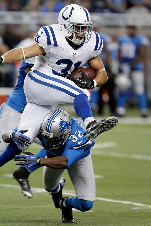 . Indianapolis Colts running back Donald Brown (31) jumps over Detroit Lions defensive back Don Carey (32) during the fourth quarter of an NFL football game at Ford Field in Detroit, Sunday, Dec. 2, 2012. (AP Photo/Duane Burleson)
