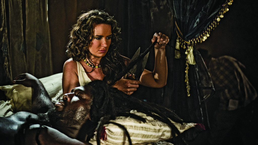 . Scene 3/67 - Int Delilah\'s House - Bedroom; Delilah (KIERSTON WAREING) is snipping away at Samson\'s (NONSO ANOZIE) hair. © Lightworkers Media / Hearst Productions Inc.