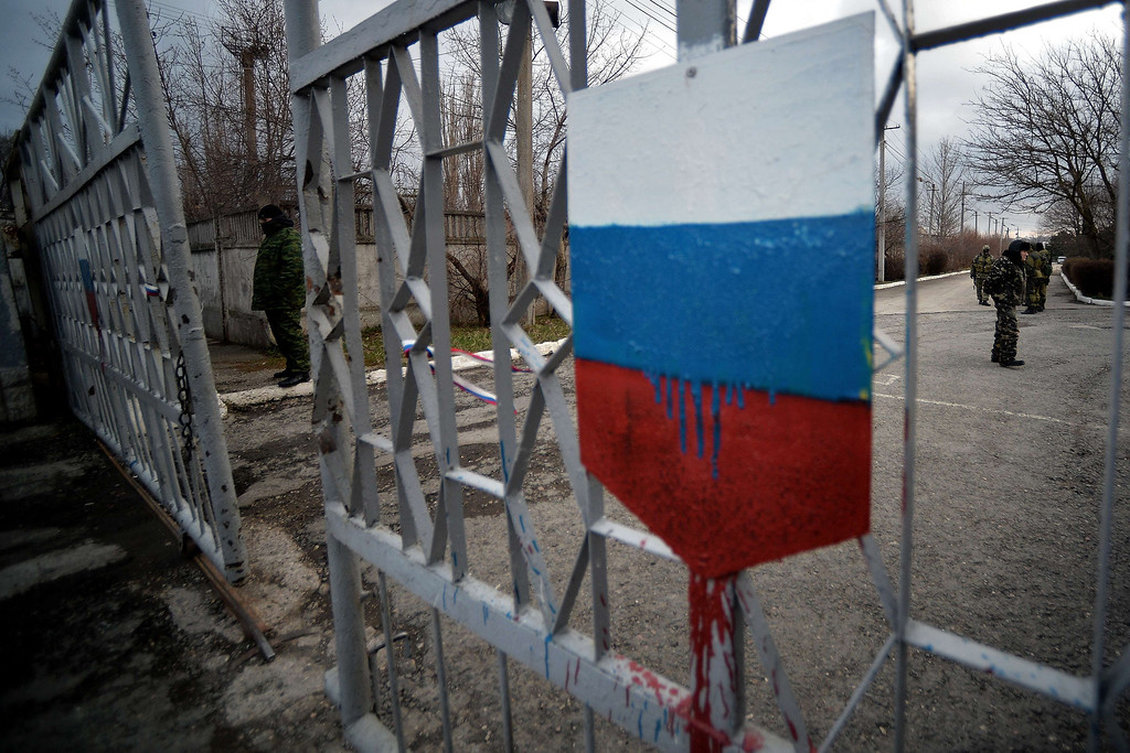 ". Members of the new pro-Russian forces dubbed the ""military forces of the autonomous republic of Crimea\"" stand at the gate, adorned with a Russian flag, of  Simferopol\'s republican military enlistment complex on March 10, 2014. Crimea\'s pro-Russian authorities sought to boost their claim to break from Ukraine Monday as volunteer soldiers swore an oath of allegiance in front of prime minister Sergei Aksyonov. He told journalists 186 volunteers had so far joined the new Crimean \""self-defense\"" units after pro-Moscow forces took power in the region and announced their intention to join with Russia, with a referendum planned for Sunday.     FILIPPO MONTEFORTE/AFP/Getty Images"