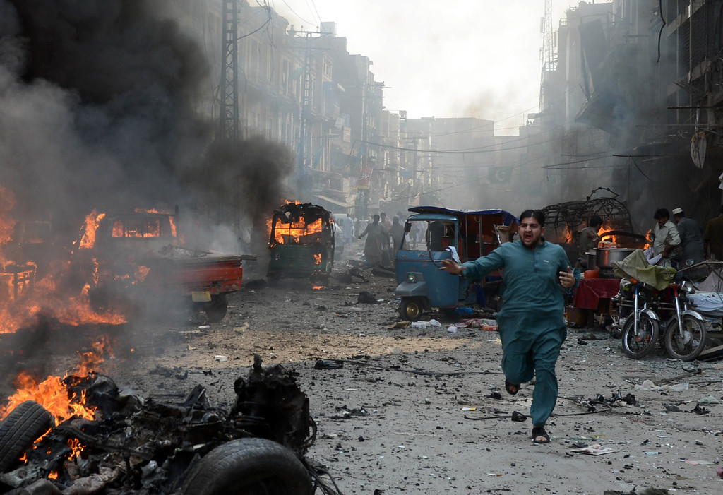 . A Pakistani man runs past burning vehicles at the site of a bomb explosion in the busy Kissa Khwani market in Peshawar on September 29, 2013. A bomb explosion killed at least 31 people in Pakistan\'s northwestern city of Peshawar, officials said -- the third deadly strike to hit the city in the last week.  AFP PHOTO / HASHAM AHMED/AFP/Getty Images
