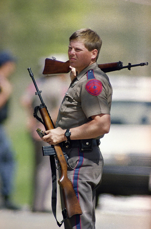 . A Texas Department of Public Safety officer holds two rifles at a checkpoint near the Branch Davidian Mount Carmel compound in Waco, Texas on Friday, March 26, 1993. The siege in its 27th day. (AP Photo/George Widman)