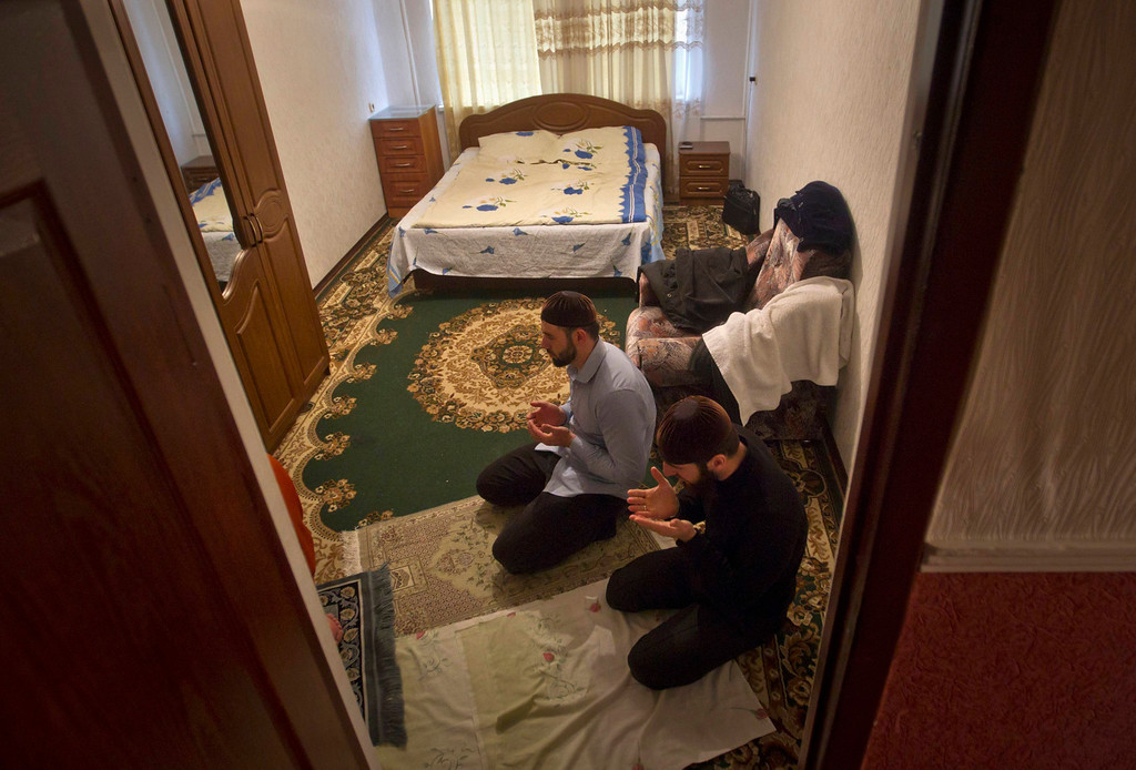 . Anzor and Salakhutdin, students at the Russian Islamic University, pray in their flat in the Chechen capital Grozny April 23, 2013.  The naming of two Chechens, Dzhokhar and Tamerlan Tsarnaev, as suspects in the Boston Marathon bombings has put Chechnya - the former site of a bloody separatist insurgency - back on the world\'s front pages. Chechnya appears almost miraculously reborn. The streets have been rebuilt. Walls riddled with bullet holes are long gone. New high rise buildings soar into the sky. Spotless playgrounds are packed with children. A giant marble mosque glimmers in the night. Yet, scratch the surface and the miracle is less impressive than it seems. Behind closed doors, people speak of a warped and oppressive place, run by a Kremlin-imposed leader through fear.    Picture taken April 23, 2013.   REUTERS/Maxim Shemetov