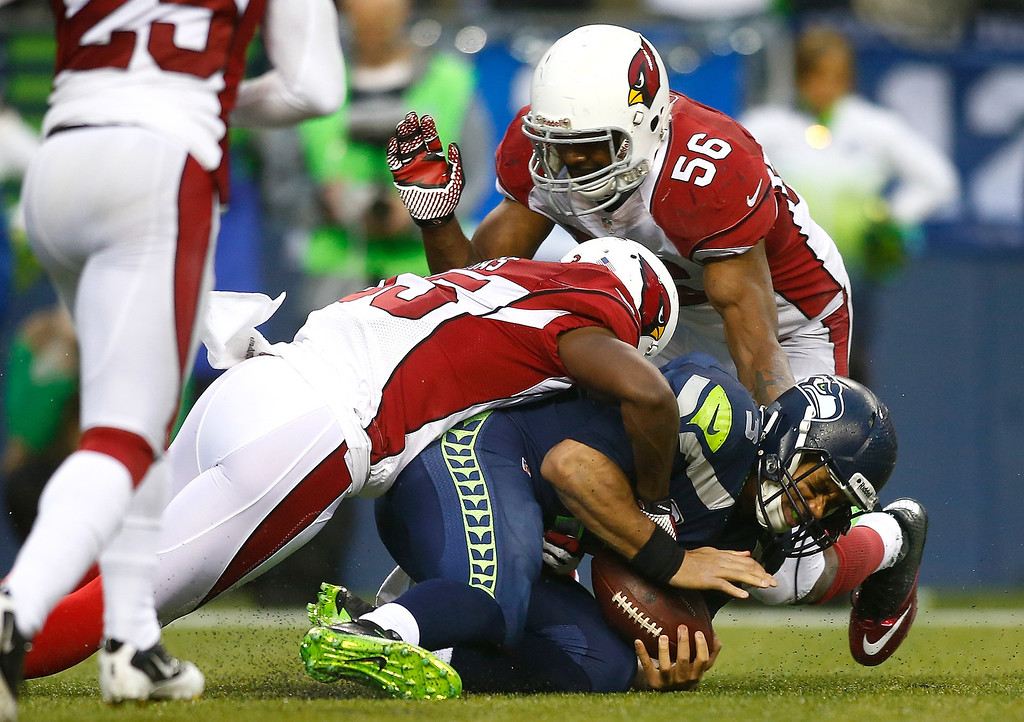 . Russell Wilson #3 of the Seattle Seahawks is sacked by Javier Arenas #35 of the Arizona Cardinals on December 22, 2013 at CenturyLink Field in Seattle, Washington.  (Photo by Jonathan Ferrey/Getty Images)