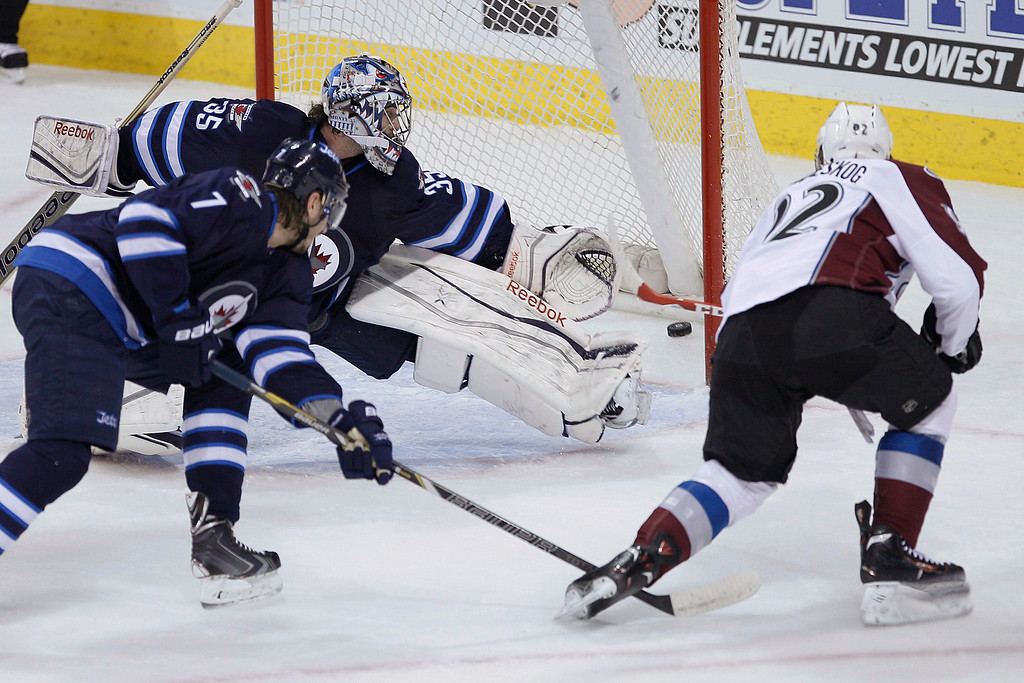 . Colorado Avalanche\'s Gabriel Landeskog (92) rips the puck past Winnipeg Jets\' goaltender Al Montoya (35) for a goal as Jets\' Keaton Ellerby (7) defends during the first period of an NHL hockey game Wednesday, March 19, 2014, in Winnipeg, Manitoba. (AP Photo/The Canadian Press, John Woods)