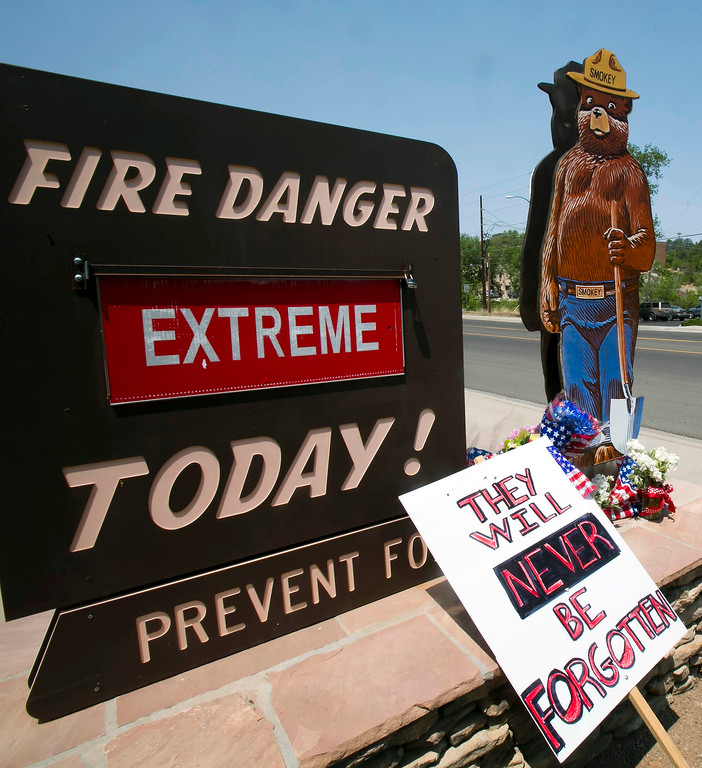 . Signs are displayed at a makeshift memorial at the fire station Monday, July 1, 2013, in Prescott, Ariz., where the elite team of firefighters was based.  (AP Photo/The Arizona Republic, Patrick Breen)