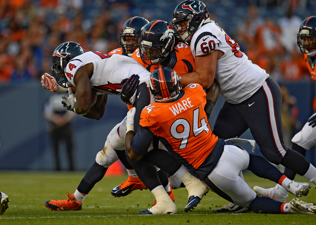 . DENVER, CO - AUGUST 23: Denver Broncos defensive end DeMarcus Ware (94) brings down Houston Texans running back Alfred Blue (44) during the first quarter August 23, 2014 at Sports Authority Field at Mile High Stadium. (Photo by Kent Nishimura/The Denver Post)