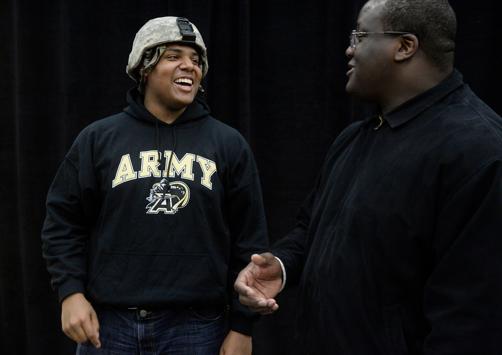 . HIGHLANDS RANCH, CO. - FEBRUARY 05: Valor Christian High School football player, Isaiah Holland, left, has a laugh with his father, Darius, while wearing an Army combat helmet, after the National Letter of Intent Day assembly at Valor Wednesday morning, February 05, 2014. Isaiah signed with the United States Military Academy at West Point. (Photo By Andy Cross / The Denver Post)