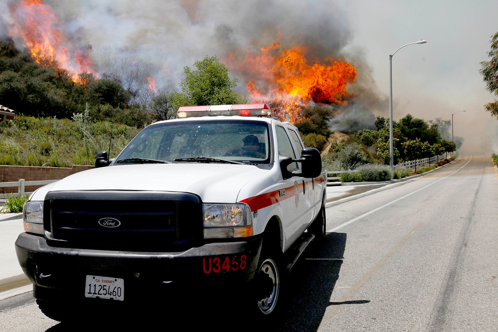 . A Ventura County Firefighter  drives  near  a hotspot as smoke and fire billows over a hill near Thousand Oaks, Calif. on Thursday, May 2, 2013.   (AP Photo/Nick Ut)