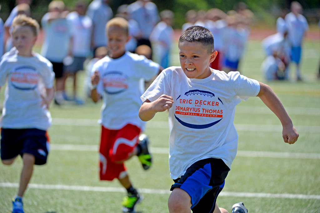 . Dominic Esquibel 8, eyes the finish line for a first place win duirng a race at football camp. Demaryius Thomas and Eric Decker team up with ProCamps for their football camp held at Littleton High School July 11, 2013. (Photo By John Leyba/The Denver Post)