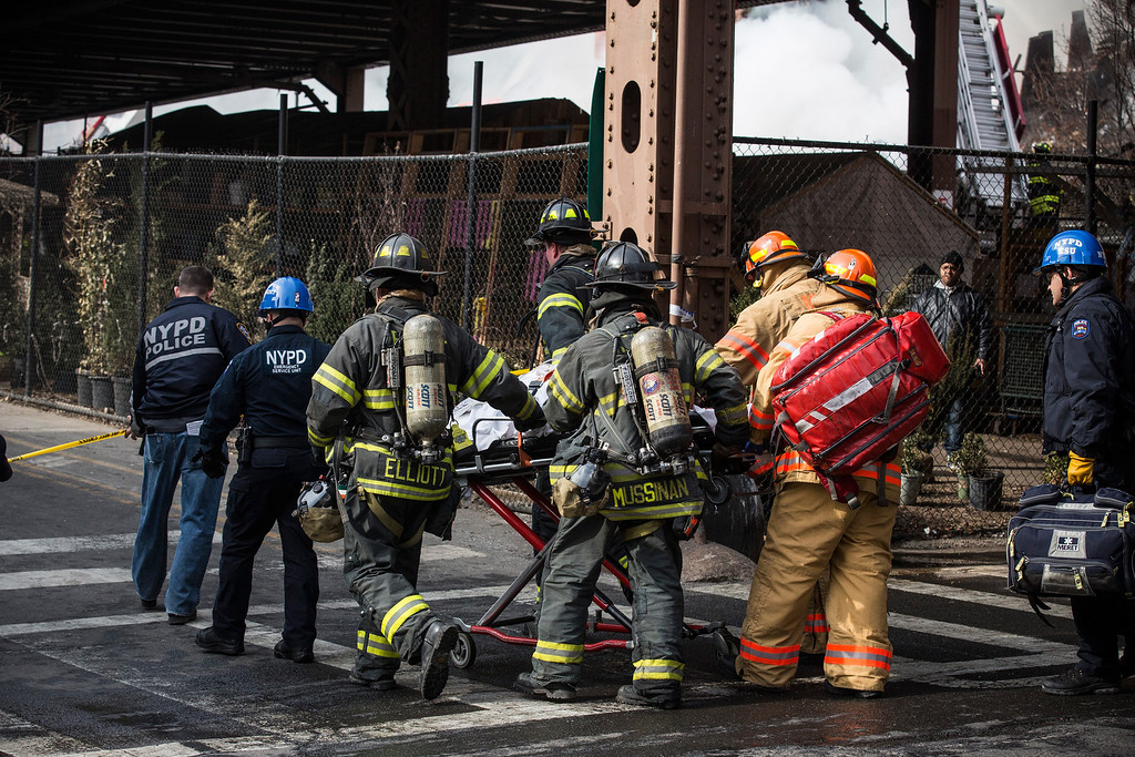 . Firefighters from the Fire Department of New York (FDNY) respond to a 5-alarm fire and building collapse at 1646 Park Ave in the Harlem neighborhood of Manhattan March 12, 2014 in New York City.   (Photo by Andrew Burton/Getty Images)