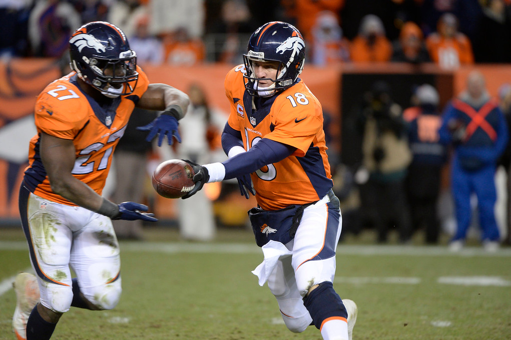. Denver Broncos quarterback Peyton Manning (18) hands off to Denver Broncos running back Knowshon Moreno (27) in the fourth quarter. The Denver Broncos take on the San Diego Chargers at Sports Authority Field at Mile High in Denver on January 12, 2014. (Photo by Craig F. Walker/The Denver Post)