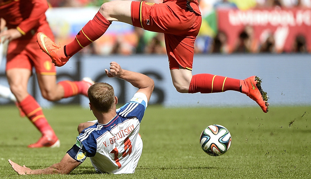 . Belgium\'s goalkeeper Simon Mignolet (TOP) vies for the ball with  Russia\'s defender Vasili Berezutski, during a Group H football match between Belgium and Russia at the Maracana Stadium in Rio de Janeiro during the 2014 FIFA World Cup on June 22, 2014.  AFP PHOTO / MARTIN BUREAU