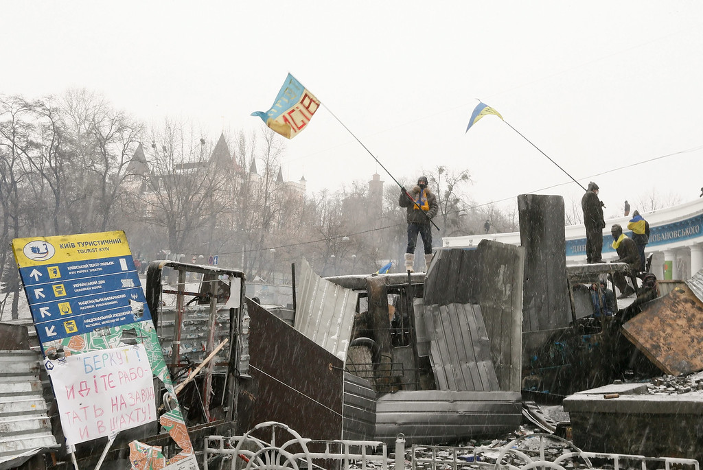. Ukrainians wave flags on a barricade during an anti-government protest in downtown Kiev, Ukraine, 21 January 2014.  EPA/SERGEY DOLZHENKO