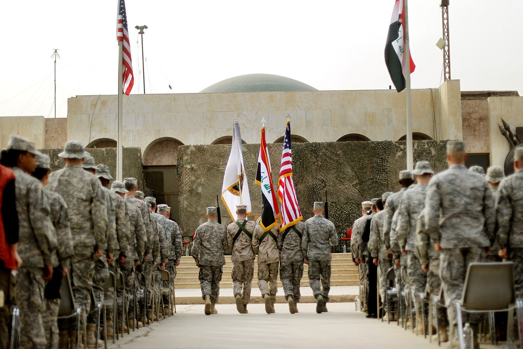 . U.S. Military personnel holding the US flag, Iraq flag, and the US Forces Iraq colors march during a casing ceremony where the United States Forces- Iraq flag was retired, signifying the departure of United States troops from Iraq, at the former Sather Air Base on December 15, 2011 in Baghdad, Iraq. United States forces were scheduled to entirely depart Iraq by December 31.  (Photo by Mario Tama/Getty Images)