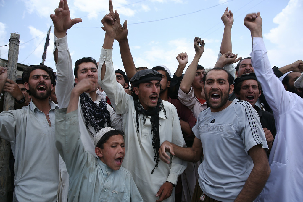 . Afghan men shout slogans against Taliban and Pakistan at the site of a suicide attack in the Urgun town of Paktika province, Afghanistan, Wednesday, July 16, 2014. The suicide bomber near a busy market and a mosque happened on Tuesday and killed dozens in the deadliest insurgent attack on civilians since the 2001 U.S.-led invasion. (AP Photo/Massoud Hossaini)