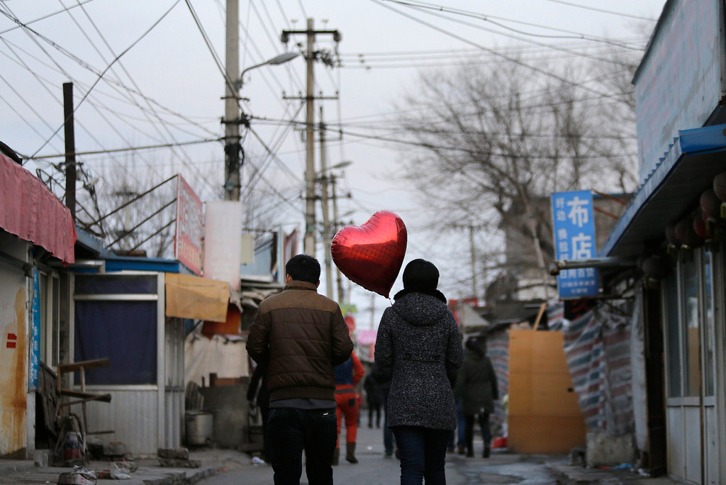 . A woman holding a heart-shaped balloon walks with her partner at a residential area for migrant workers on Valentine\'s Day in Beijing February 14, 2013. REUTERS/Jason Lee