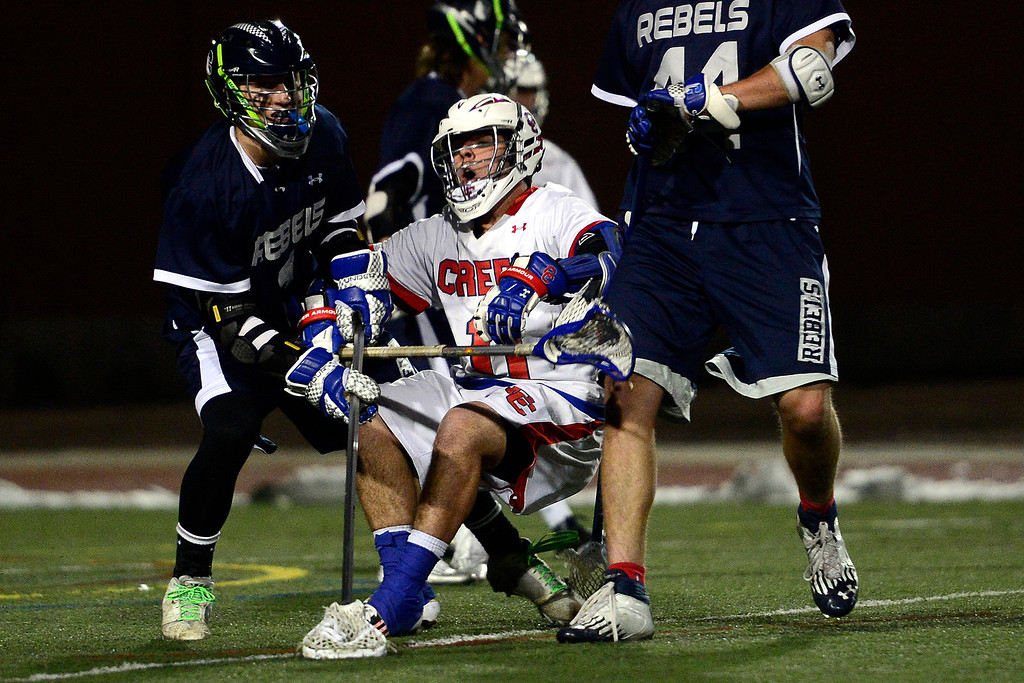 . Cherry Creek\'s Trip Dehaven gets checked by Columbine\'s Ian Lewis during Cherry Creek\'s 7-6 win.  (Photo by AAron Ontiveroz/The Denver Post)