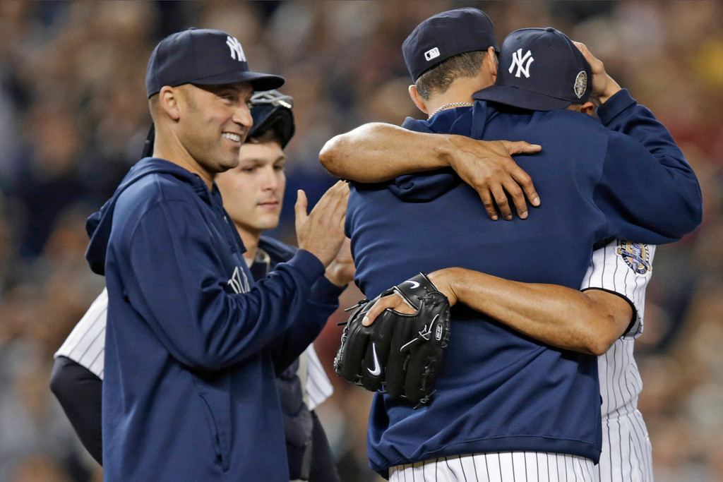 . New York Yankees\' Derek Jeter, left, applauds as retiring Yankees pitcher Andy Pettitte, back to camera, embraces relief pitcher Mariano Rivera in the ninth inning of Rivera\'s final appearance at a baseball game at Yankee Stadium, Thursday, Sept. 26, 2013, in New York. The Rays won 4-0. (AP Photo/Kathy Willens)