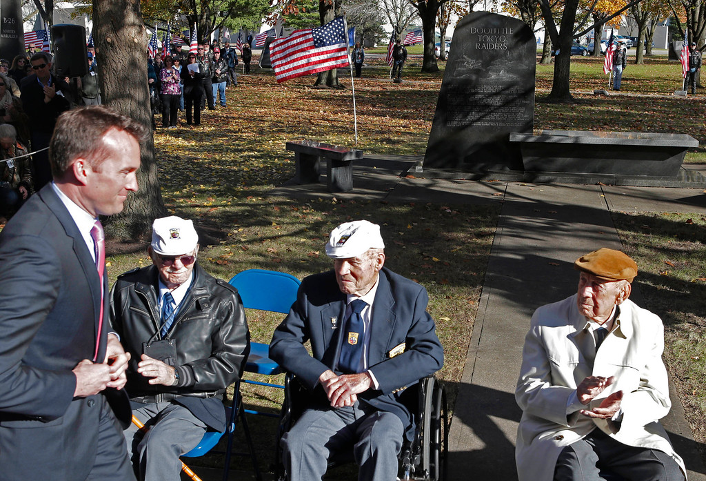 . Eric Fanning, left, acting Secretary of the US Air Force walks to the podium past three of the surviving members, seated left to right, Edward Saylor, David Thatcher, and Richard Cole, of the 1942 raid on Tokyo led by Lt. Col. Jimmy Doolittle, Saturday, Nov. 9, 2013, outside the National Museum of the US Air Force in Dayton, Ohio. The fourth surviving member, Robert Hite, was unable to travel to the ceremonies. (AP Photo/Al Behrman)