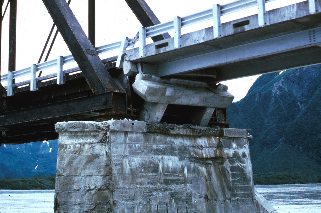 . Alaska Earthquake March 27, 1964. The earthquake shifted the steel trusses of the Copper River and Northwestern Railroad bridge near Round Island from 1 to 2 feet. This view shows one of the displaced trusses, which pounded against an adjacent steel girder span. The girder span was moved to the right, its concrete pedestal was rotated, and the girder span almost fell into the river. Note the shortening indicated by buckling of the guard rail. U.S. Geological Survey photo