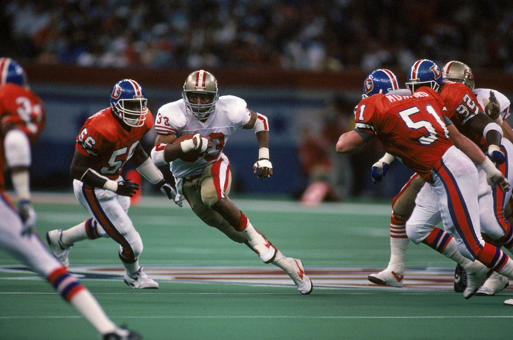 . Running back Roger Craig #33 of the San Francisco 49ers looks for room to run against Denver Broncos inside linebacker Marc Munford #54 in the second quarter of Super Bowl XXIV at Louisiana Superdome on January 28, 1990 in New Orleans, Louisiana.    (Photo by George Rose/Getty Images)