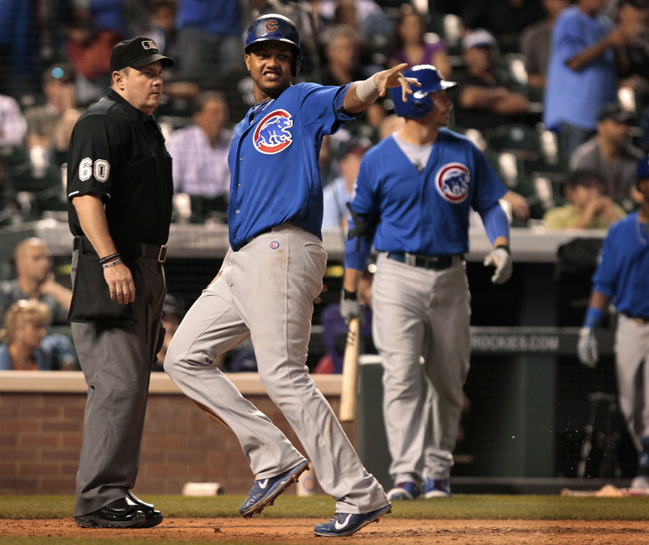 . Chicago Cubs\' Starlin Castro (13) points to first base after Castro scored on a single by Ryan Sweeney in the 11th inning of a baseball game against the Colorado Rockies in Denver on Tuesday, Aug. 5, 2014. (AP Photo/Joe Mahoney)