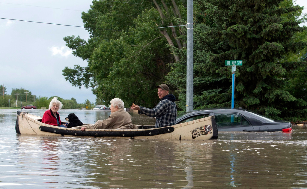. Two women are rescued from the flooding in a canoe in High River in Alberta province June 20, 2013. A state of emergency has been issued for the town of High River, which is being evacuated due to floods. REUTERS/Mike Sturk