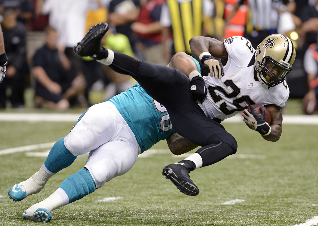 . New Orleans Saints running back Khiry Robinson (29) is thrown to the ground by Miami Dolphins defensive end Paul Soliai in the first half of an NFL football game in New Orleans, Monday, Sept. 30, 2013. (AP Photo/Bill Feig)
