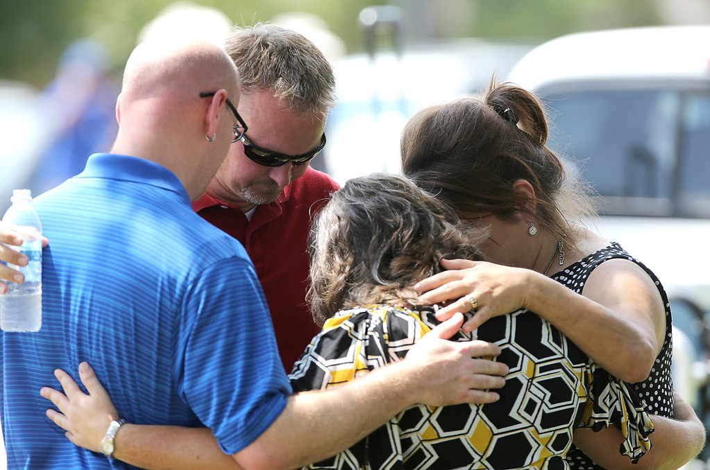 . Joel Eisenbruse, John Cordey , Rosemary Alyea and Michelle Cress, with the Trinity Church outreach, pray at the scene of a stabbing at Spring High School September 4, 2013 in Spring, Texas. (Photo by Thomas B. Shea/Getty Images)