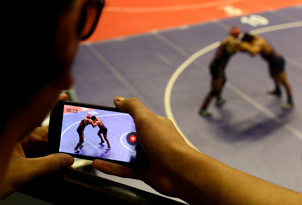 . DENVER, CO. - FEBRUARY 22ND: Wrestling fan, R.J. Torres, 16-years-old, Loveland High School sophomore, takes a cell phone video of his friend, Loveland wrestler, Dalton Weis, wrestling Trevon Beauford, Eaglecrest High School, in the 5A 182lb quarterfinal match at the  Colorado State Wrestling Championships at the Pepsi Center in Denver, Colorado, February 22nd, 2013. (Photo By Andy Cross / The Denver Post)